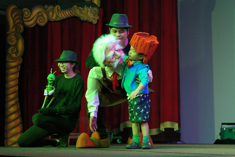 Pinocchio theatre presentation with old man puppet, a child, woman and a man on stage in Artbeatz
