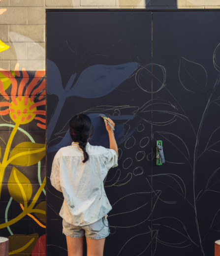 A woman painting a plant on the wall at Artbeatz art class